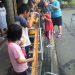 施工現場の後ろで、夏休みの子供たちが流しそうめん。楽しそう